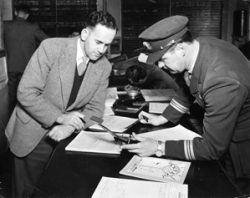 An officer assists a pilot compile his flight plan in the Melbourne/Essendon Briefing Office c. 1949
