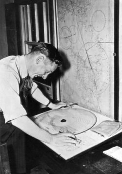 A Melbourne Control Officer makes calculations at the Melbourne ACC using the Rodoniscope to calculate longitudinal separation c. 1940s.
